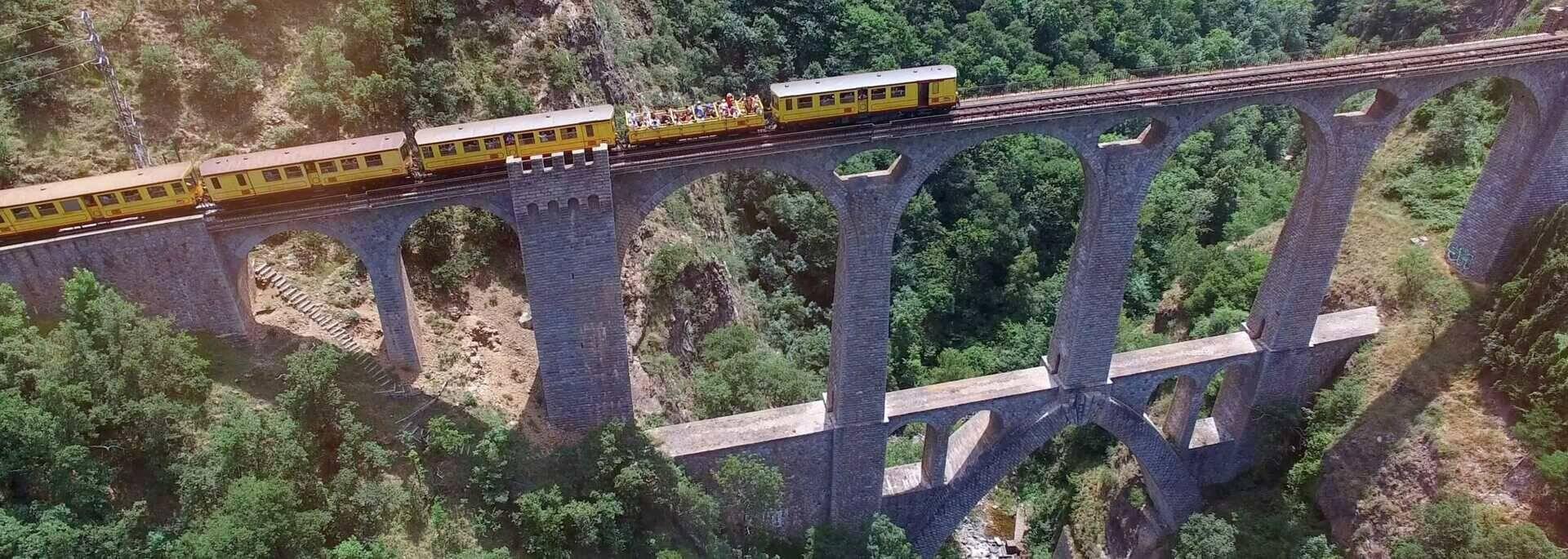 train jaune sur le pont séjourné